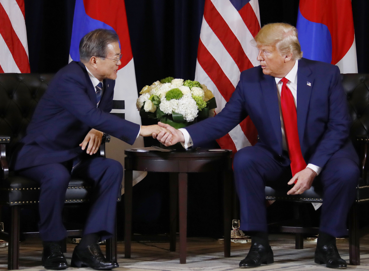 President Moon Jae-in (left)talks with US President Donald Trump during their summit at a New York hotel on Monday. (Yonhap)