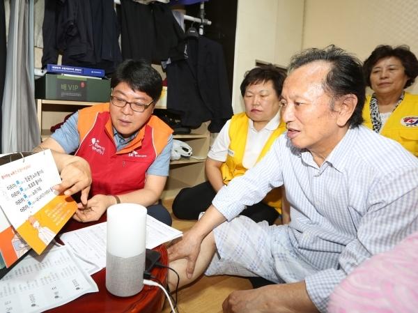 SKT official explain how to use the smart speaker Nugu to a senior citizen living alone. SKT