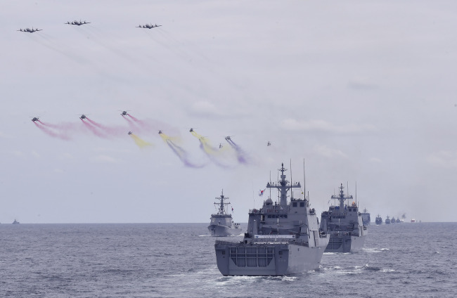 Escorted by patrol aircraft and anti-submarine helicopters, South Korean combat vessels rehearse maneuvers ahead of Jeju International Fleet Review in October last year. (Republic of Korea Navy)