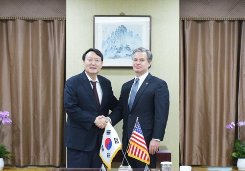 South Korea`s Prosecutor General Yoon Seok-youl (L) shakes hands with US Federal Bureau of Investigation (FBI) Director Christopher Wray ahead of talks in Seoul on Sept. 24, 2019, in this photo provided by the Supreme Prosecutors` Office. (Yonhap)