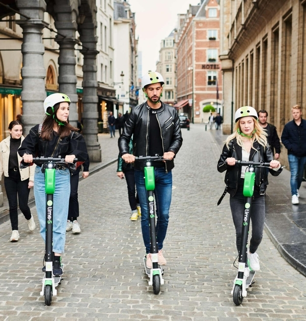 People riding e-scooters on the street Lime