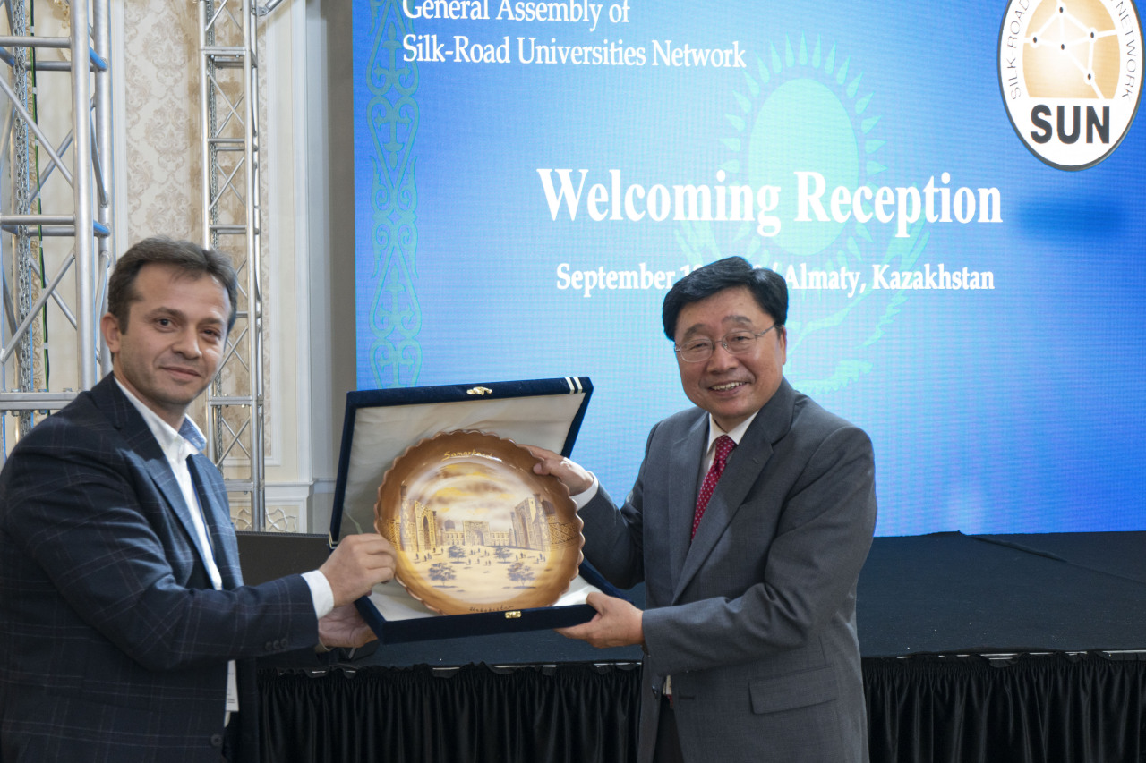 Azamat Akbarov (left), vice rector of the Silk Road International University of Tourism in Samarkand, Uzbekistan, presents a souvenir to professor Hwang Sung-don, secretary general of the Silk Road Universities Network, at a welcoming reception for the participants in the network's fifth general assembly in Almaty, Kazakhstan, on Sept. 17. Courtesy of SUN