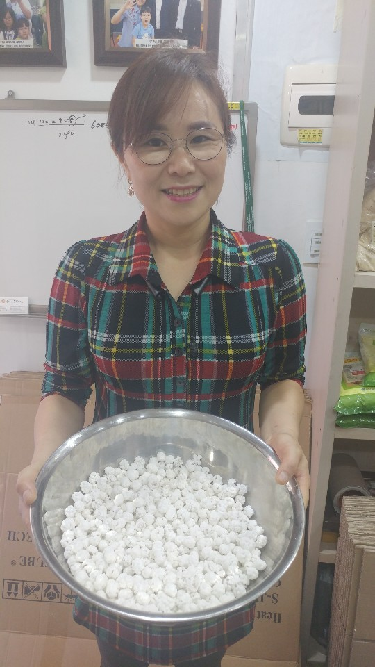 Hong Eun-hye holds a bowl of North Korean bean candies at her shop in Incheon on Monday. (The Korea Herald)