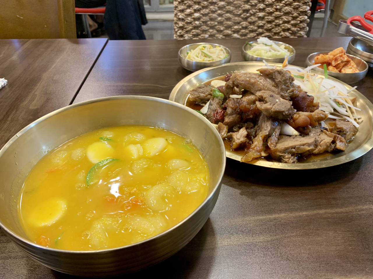 Rice cake soup with ground potato (left) and steamed pig's leg. (Im Eun-byel/The Korea Herald)