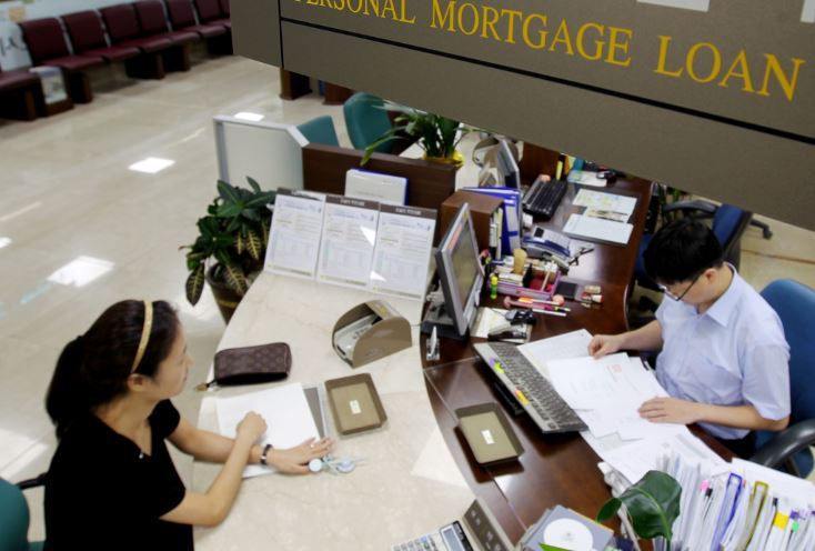 A commercial bank teller deals with a customer for the mortgage loan process. (Yonhap)