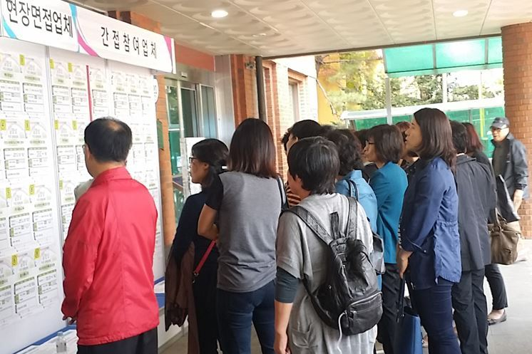 Job seekers look at a bulletin board on which companies post recruitment notices for the middle-aged and elderly in Guri, Gyeonggi Province. (Gyeonggi Provincial Office)