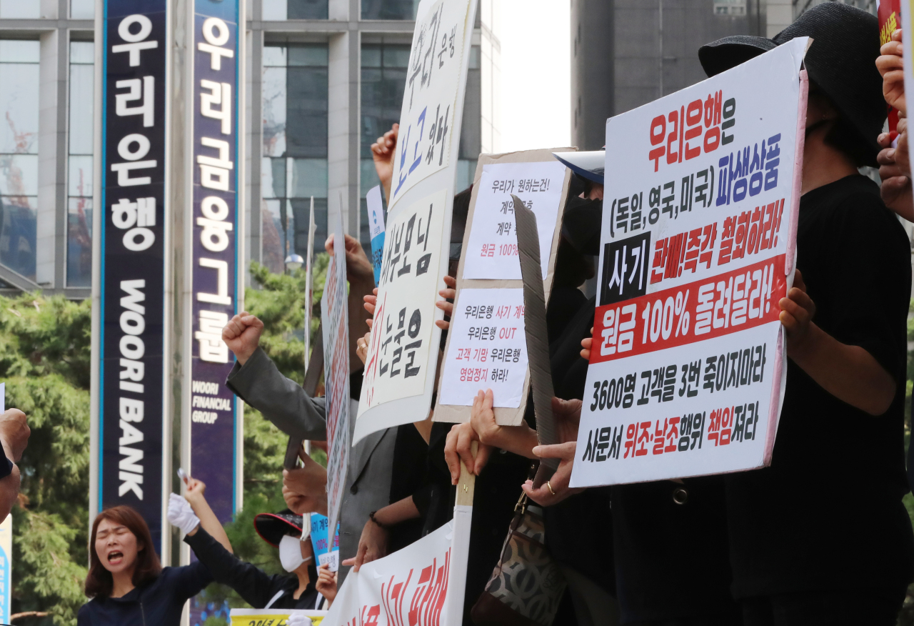 Investors of derivatives-linked securities products sold by Woori Bank protest in front of the bank`s headquarters in central Seoul on Tuesday. (Yonhap)