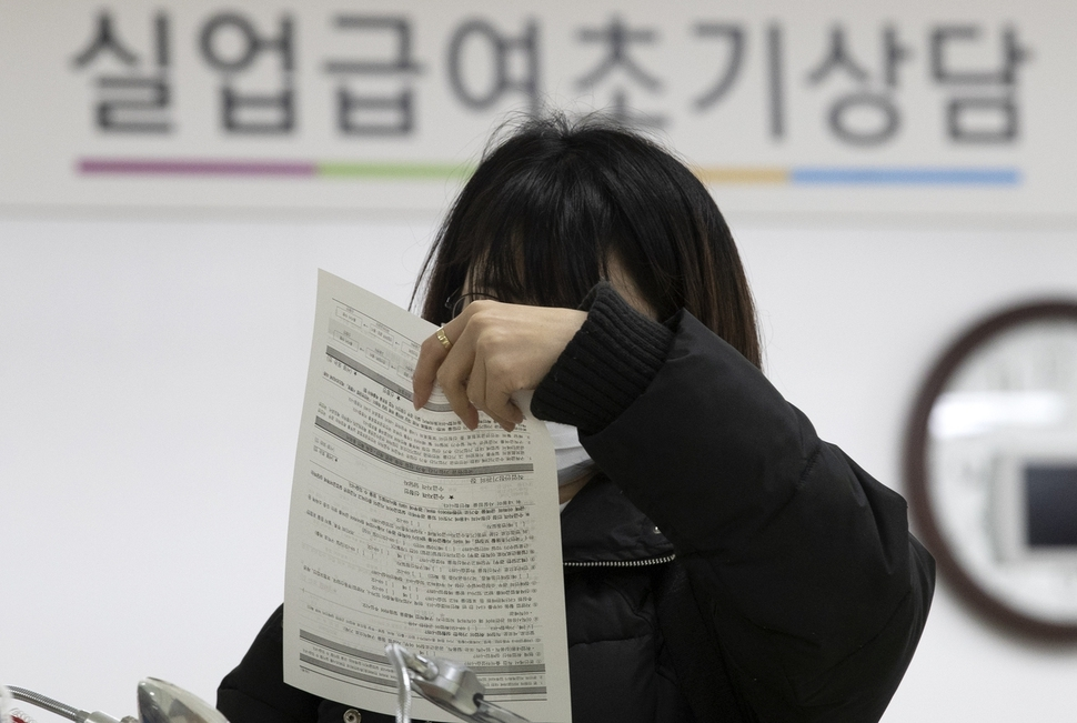 A citizen looks at her application form for unemployment benefits at a regional office of the Korea Employment Information Service in Seoul earlier this year. (Yonhap)