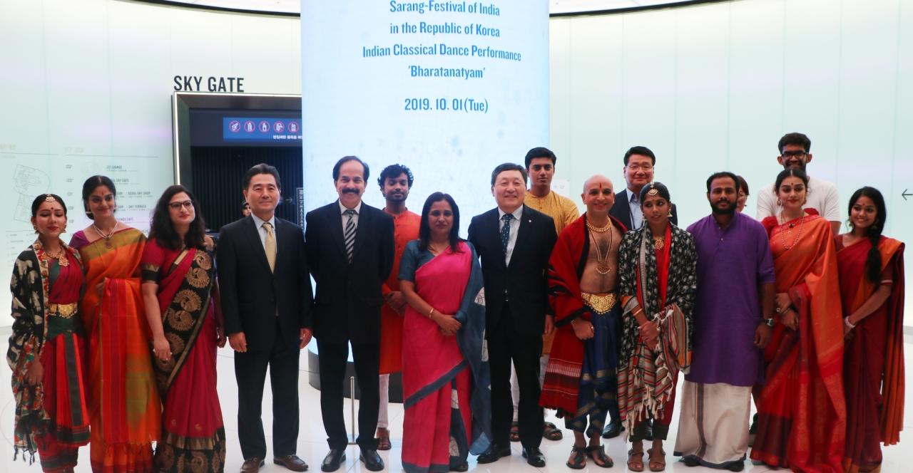 """Ambassador of India to South Korea Sripriya Ranganathan (first row, sixth from left) and Lotte World CEO Park Dong-gi (first row, seventh from left) pose with bharata natya dancers during a preview of the fifth annual """"Sarang: the Festival of India in the Republic of Korea,"""" Oct. 1 at the Lotte World Tower in southeastern Seoul. (Embassy of India)"""