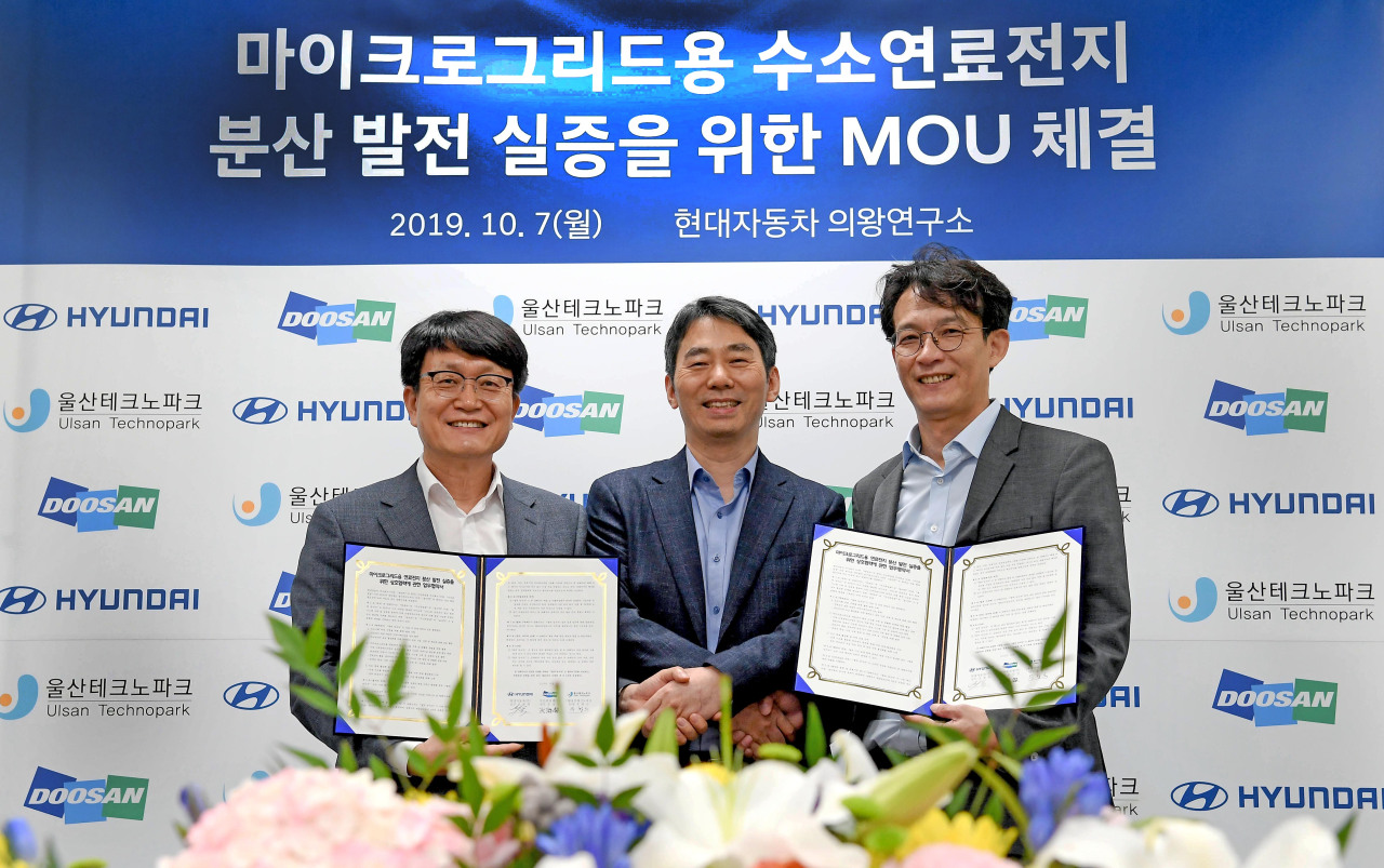 From left: Woo Hang-su, head of Ulsan TechnoPark, Oh Jae-hyuk, head of the Future Technology Group at Hyundai Motor Group and Moon Sang-jin, head of Doosan Fuel Cell's R&D and new business division, pose for a photo after signing a memorandum of understanding at Hyundai Motor Group's R&D center in Uiwang, Monday. (Hyundai Motor Group)
