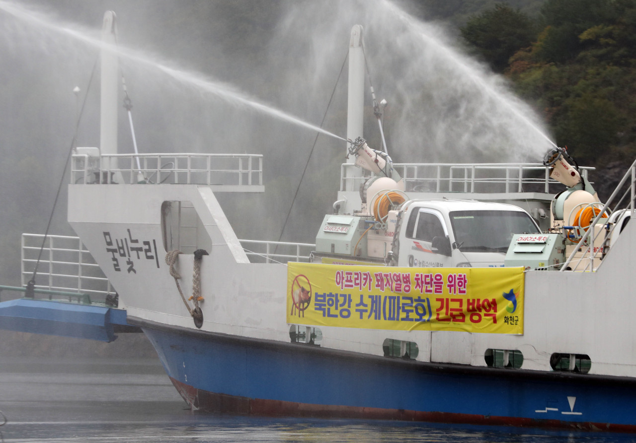 Trucks on a vessel carry out disinfection procedures Oct. 2 in the Lake Paro district, located in Gangwon Province's Yanggu and Hwacheon counties, in an effort to prevent the spread of African swine fever. (Yonhap)