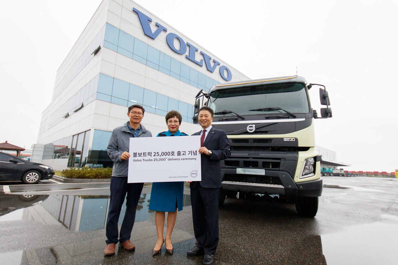 Volvo Trucks Korea CEO Kim Young-jae (right) poses for a photo at an event to mark the company's 25,000th delivery to Kim Hye-kyung (center) at its central cargo center in Pyeongtaek, Gyeonggi Province, Monday. Volvo Trucks Korea