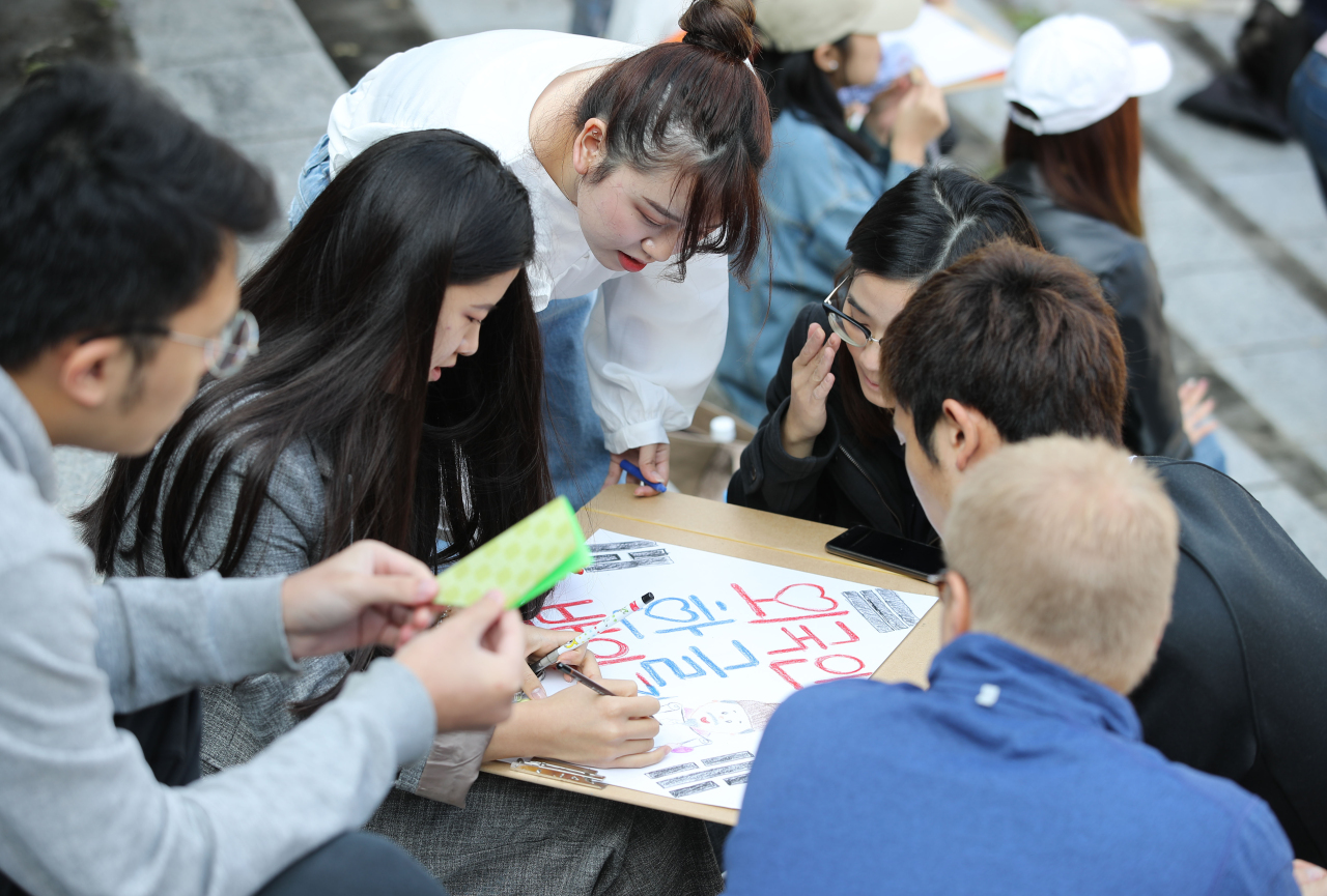 Foreigners and overseas Koreans participate in a calligraphy writing contest at the 28th Hangeul Essay Contest for Foreigners held Tuesday at Yonsei University in Seodaemun-gu, Seoul. (Yonhap)