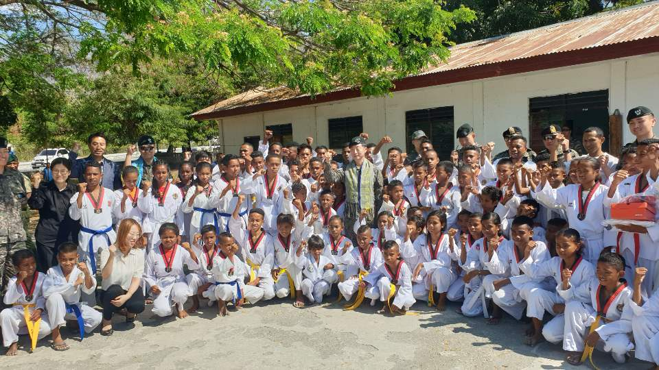 East Timorese children in Taekwondo uniforms pose with South Korea's delegation in Lospalos, East Timor, on Oct. 6. (Embassy of the Republic of Korea in East Timor)