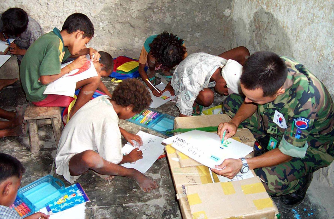 A South Korean soldier draws on a sketchbook with East Timorese children during his service in East Timor as part of the Evergreen Forces in the early 2000s. (The Korea Defense Daily)