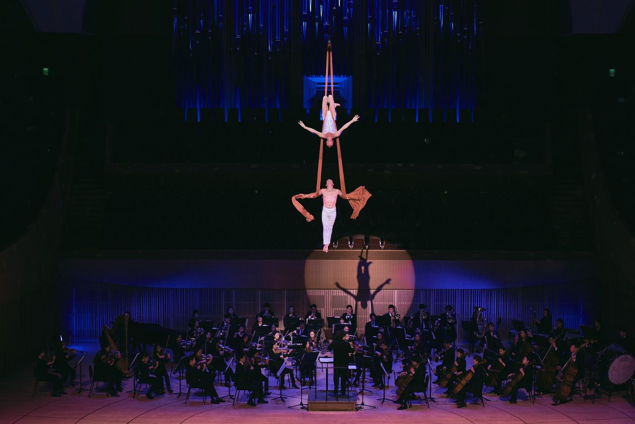 "Two aerialists fly high in the air while the orchestra plays the Valse from Tchaikovsky's ""Swan Lake."" (The Lotte Foundation for Arts)"