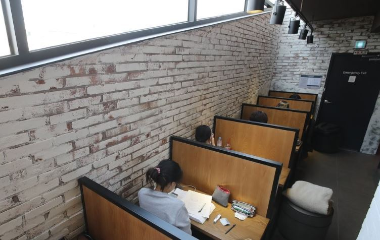 Customers at a coffee shop in Seoul sit at tables for one. (Yonhap)