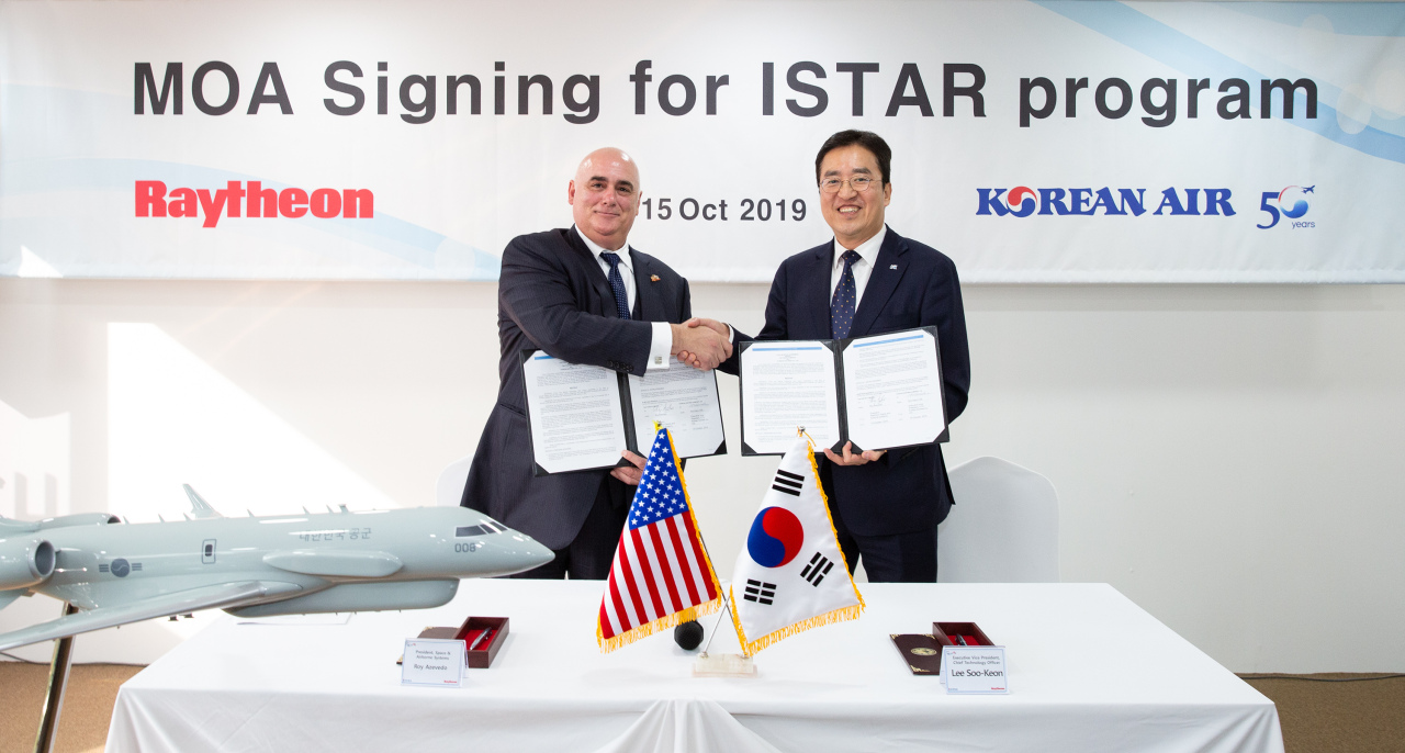 Korean Air Executive Vice President and Chief Technology Officer Lee Soo-keun (right) and Raytheon Space and Airborne Systems President Roy Azevedo pose for a photo after signing an exclusive collaboration agreement during the Seoul International Aerospace and Defense Exhibition at Seoul Air Base in Seongnam, Gyeonggi Province, Tuesday.(Korean Air)