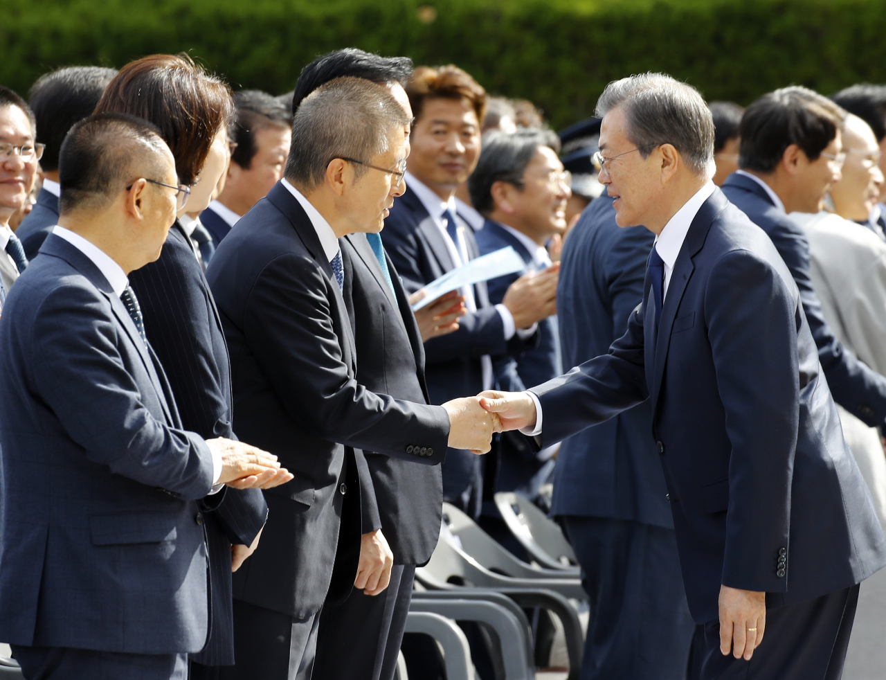 President Moon Jae-in shakes hands with Hwang Kyo-ahn, chairman of main opposition Liberty Korea Party, at the Busan-Masan Democratic Protests event in Busan on Wednesday. Yonhap
