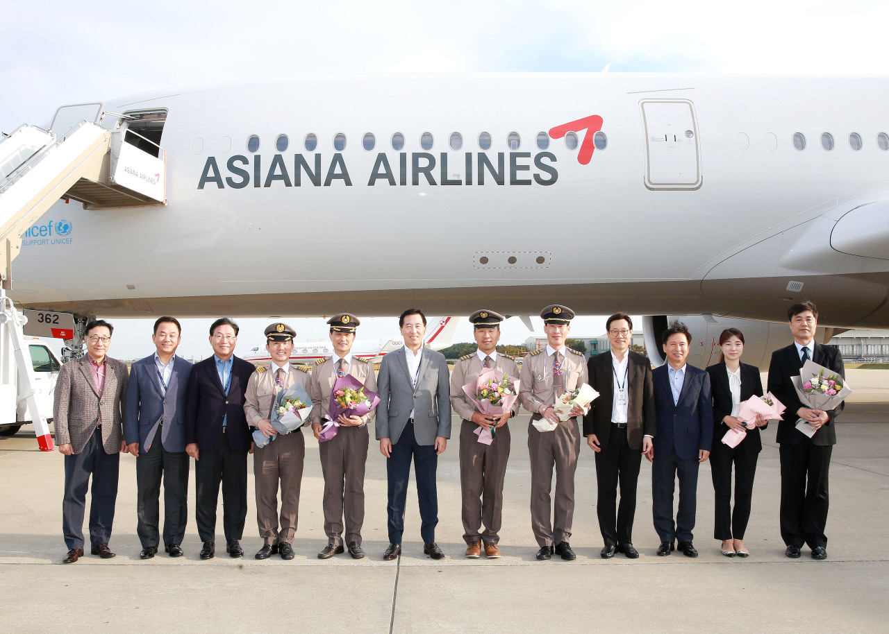 Asiana Airlines CEO Han Chang-Soo (sixth from left) poses with Asiana employees for a photo to celebrate introduction of its 10th A350-900 for operation. (Asiana Airlines)