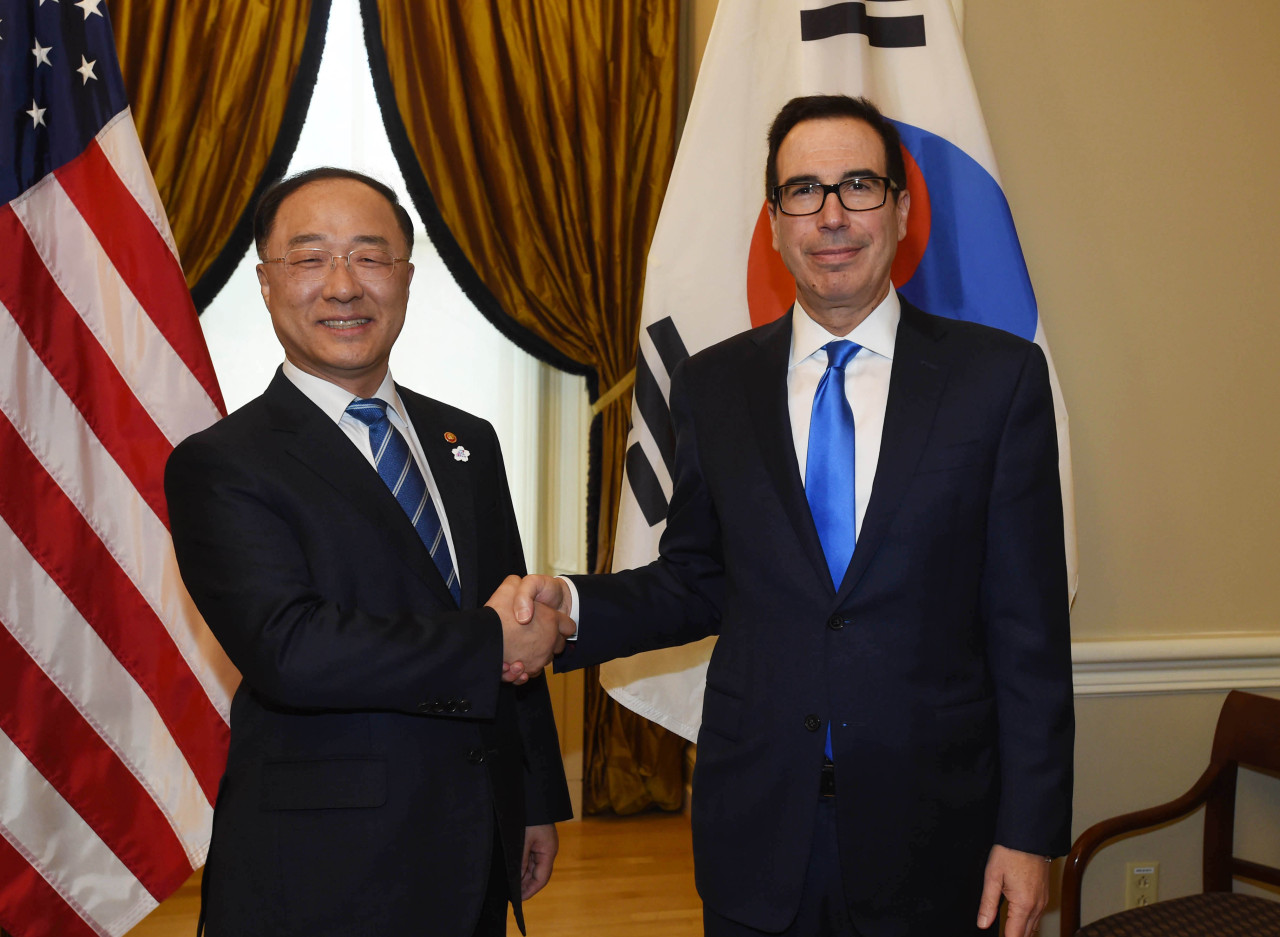 cap: Deputy Prime Minister and Finance Minister Hong Nam-ki (left) shakes hands with US Treasury Secretary Steven Mnuchin in Washington on Friday. (Yonhap)