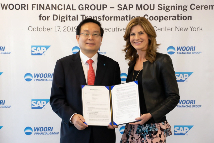 Woori Financial Group Chairman Sohn Tae-seung, left, signs an MOU with SAP CEO Jennifer Morgan at the SAP Executive Briefing Center in New York on Thursday (local time). (Woori Financial Group)