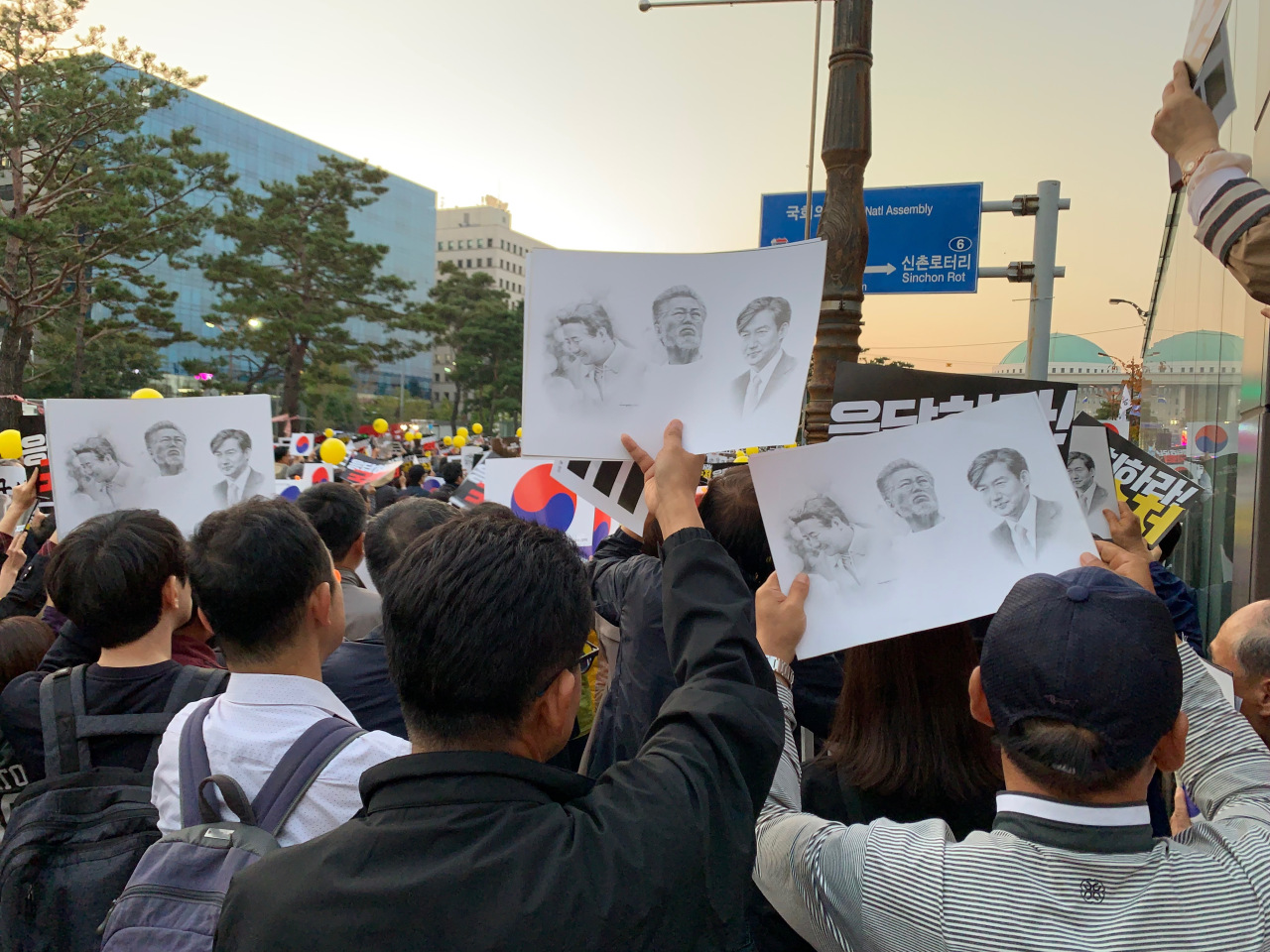 Protesters wave banners with faces of Cho, Moon and Roh. (Kim Arin/The Korea Herald)