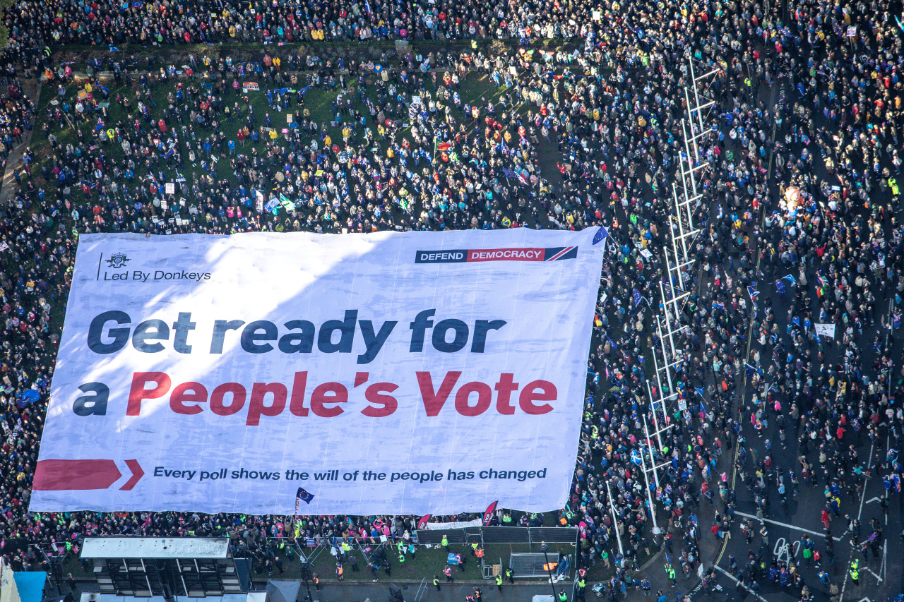 An aerial view shows Brexit accountability campaign group Led By Donkeys unfurling a large crowd banner, as a spoof of the government's advertising campaign, at Parliament Square, London, Britain October 19, 2019 (Reuters)