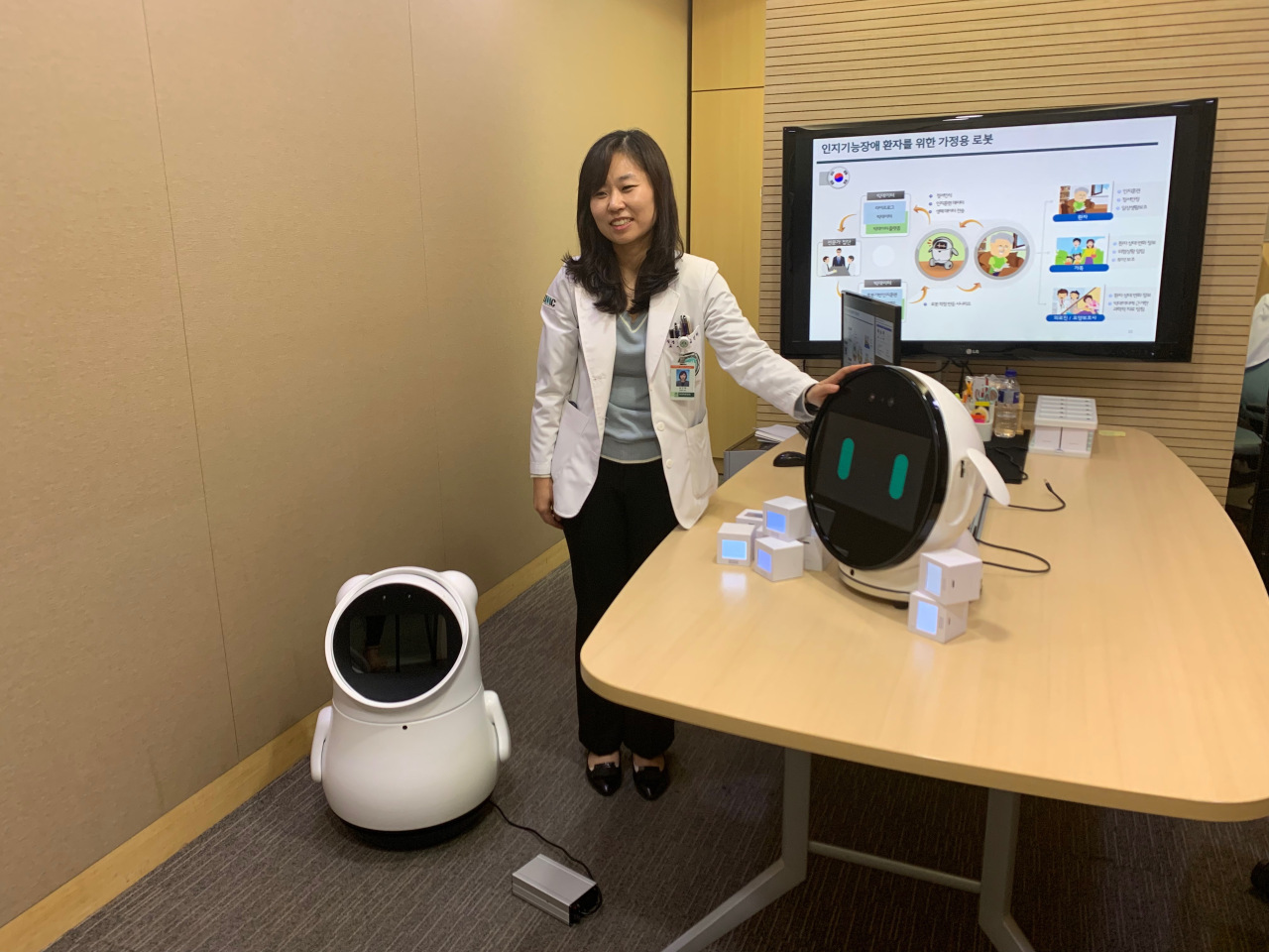 Ewha Womans University Medical Center neurologist Kim Geon-ha poses with cognitive training robot Bomy. (Kim Arin/The Korea Herald)