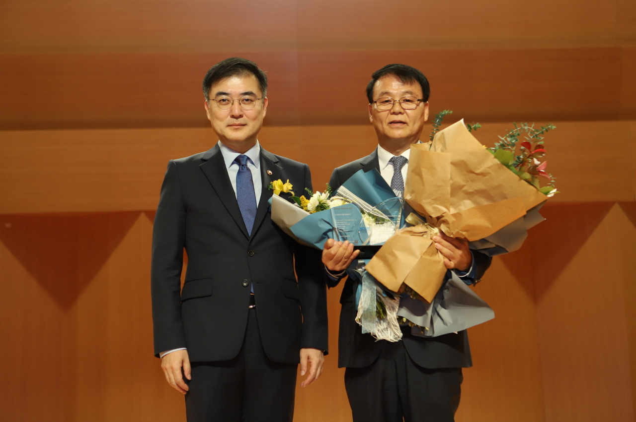 KT&G Vice President Kim Tae-sub (right) poses for a photo after receiving the top corporate governance award from Korea Corporate Governance Service in Seoul on Tuesday. (KT&G)