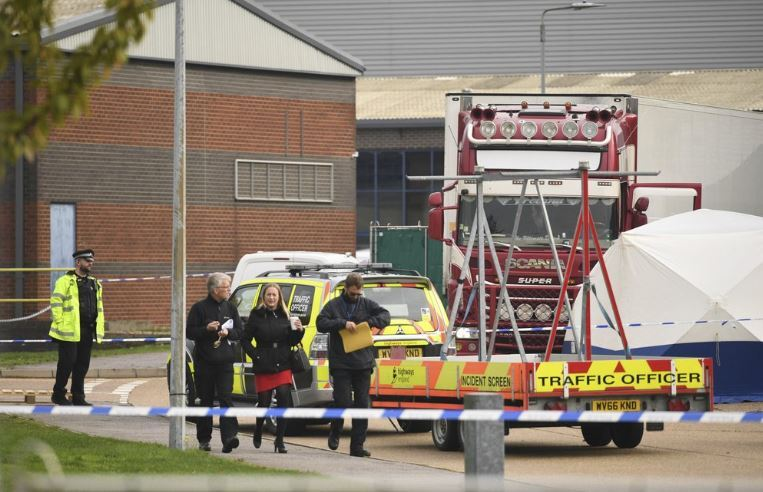 People walk past a police officer at the scene after a truck, seen in rear, was found to contain a large number of dead bodies, in Thurrock, South England, early Wednesday Oct. 23, 2019. Police in southeastern England said that 39 people were found dead Wednesday inside the truck container believed to have come from Bulgaria. (AP)