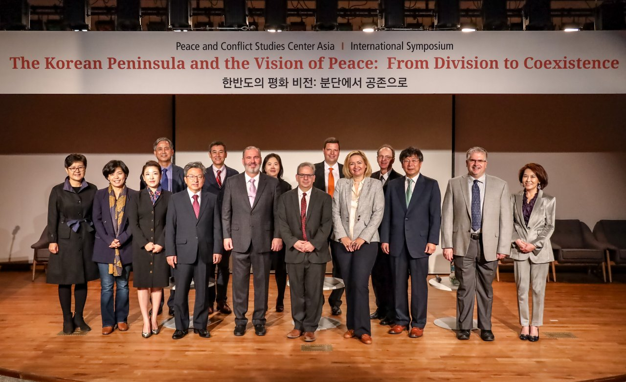 """Participants pose for a photo at """"The Korean Peninsula and the Vision of Peace: From Division to Coexistence,"""" an annual symposium hosted by George Mason University at its campus in Incheon, Wednesday. (George Mason University)"""