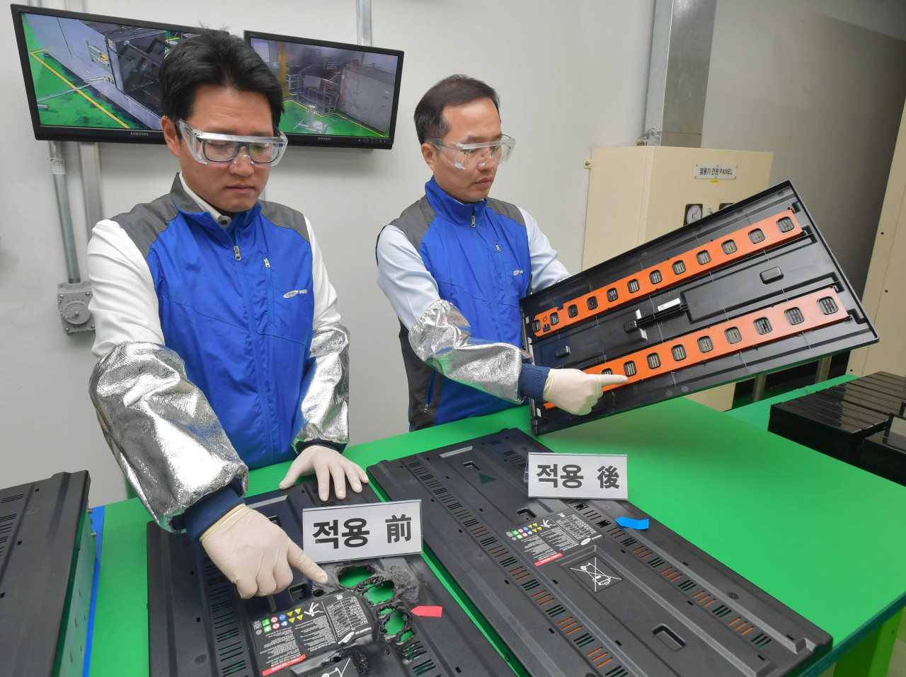 Samsung SDI officials demonstrate how the extinguishing system works at a test room at its Ulsan plant on Wednesday. (Samsung SDI)
