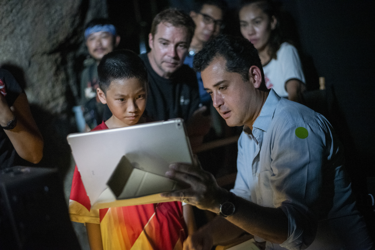 """The Cave"" director Tom Waller (right) works with a child actor on the set of the film in Thailand. (De Warrenne Pictures)"