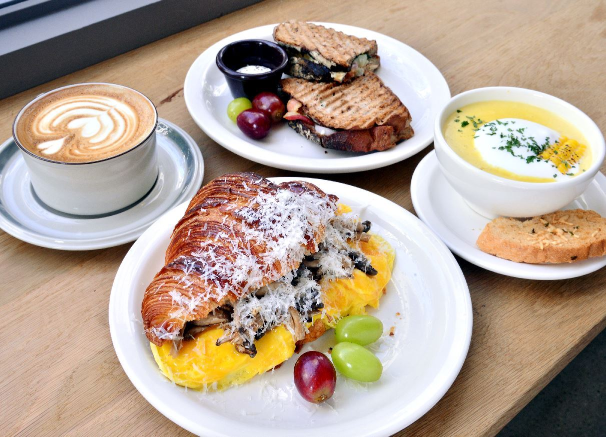 Sunset Swimming Sandwich specializes in hot sandwiches, soup and coffee like their truffle egg croissant (front), potato bacon panini (back), rich corn soup (right) and creamy and potent latte (left). (Park Hyun-koo/The Korea Herald)