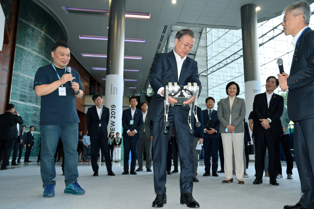 President Moon Jae-in (center) demonstrates how to use a robotic cheetah when he attends Naver's 2019 Deview conference held at Coex conference hall in Seoul Monday. Standing left to Moon is Seok Sang-ok, who leads Naver's research and development unit, Naver LABS. (Naver)