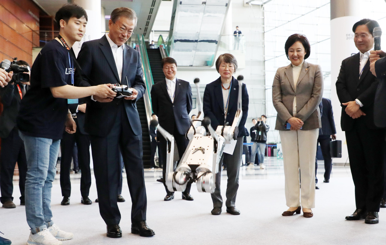 President Moon Jae-in tests a robot in Seoul on Monday. Yonhap