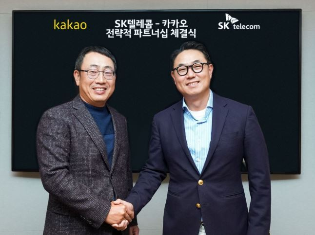 SKT's Mobile Network Operation Division chief Yoo Young-sang(left) shakes hands with Kakao's co-chief Yeo Min-soo. Yonhap