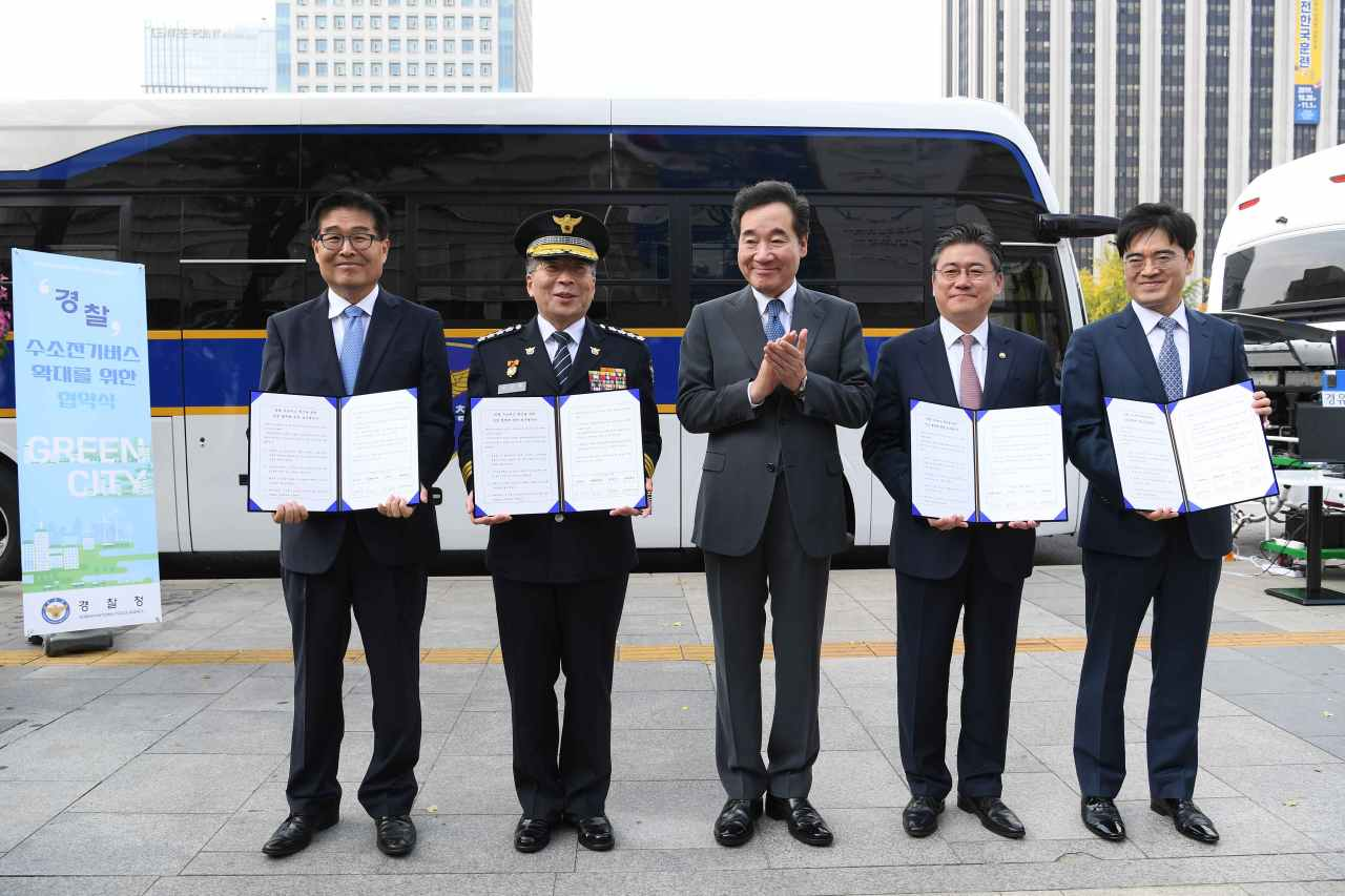 From left: Environment Ministry's Air Quality Policy Bureau head Chung Bok-young, Korean National Police Agency Commissioner General Min Gab-ryong, Prime Minister Lee Nak-yon, Vice Industry Minister Chung Seung-il, and Hyundai Motor President Kong Young-woon pose for a photo after signing an MOU for development and operation of hydrogen-powered buses for the Korean police at Gwanghwamun, Seoul, Thursday. (Hyundai Motor)