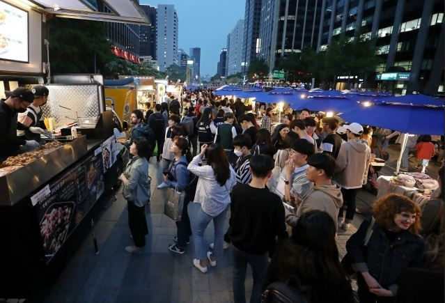 People gather at a night market in downtown Seoul earlier this year. (Yonhap)