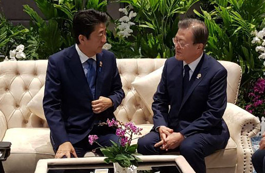 President Moon Jae-in (right) talks with Japanese Prime Minister Shinzo Abe ahead of the 22nd ASEAN Plus Three summit in Bangkok on Monday. (Yonhap)