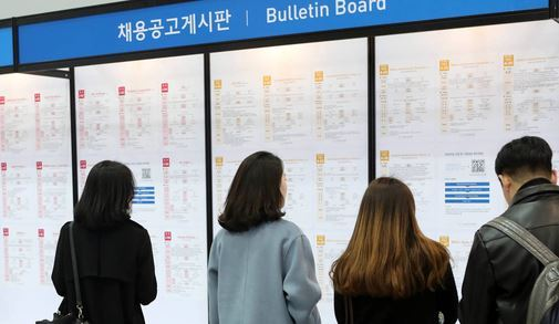 Visitors to a job fair in Seoul look at the bulletin board, which provides the list of recruiting companies. (Yonhap)