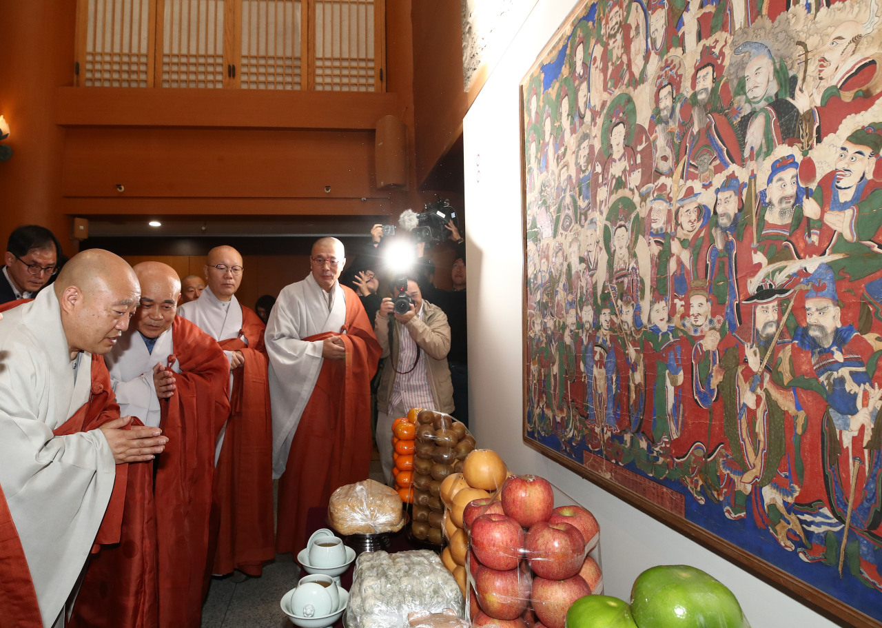 "From left: The Ven. Wonhaeng, the president of the Jogye Order of Korean Buddhism, and the Ven. Kyungsun, the abbot of Beomeosa, offer prayers in front of ""Guardian Deities of Beomeosa Temple"" at the Memorial Hall of Korean Buddhist History and Culture, central Seoul, on Tuesday. (Yonhap)"