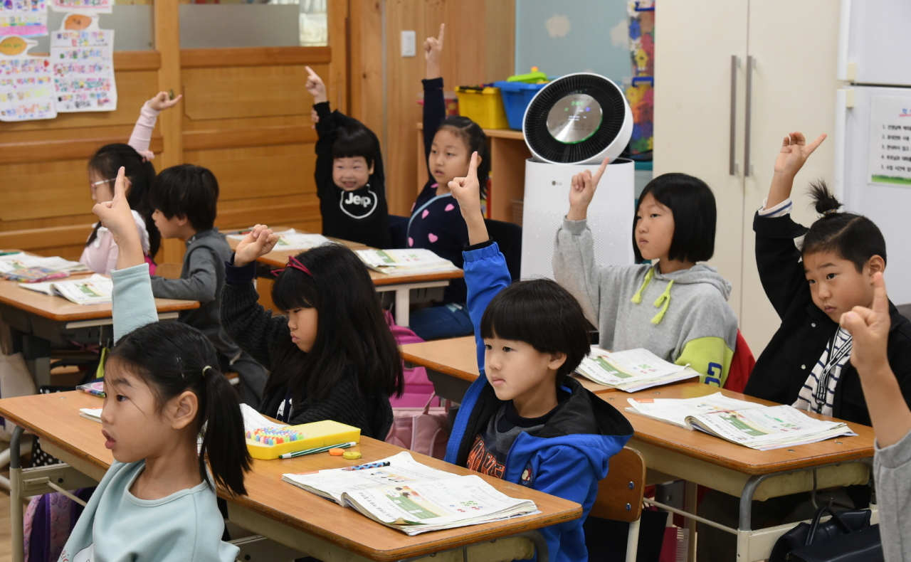 Students are shown in an elementary school classroom in Paju, Gyeonggi Province, with an LG Electronics air purifier donated by LG Group. (LG Group)
