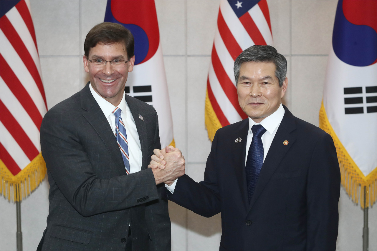South Korean Defense Minister Jeong Kyeong-doo (right) and US Secretary of Defense Mark Esper clasp hands ahead of talks at the Defense Ministry compound in Seoul. (Yonhap)