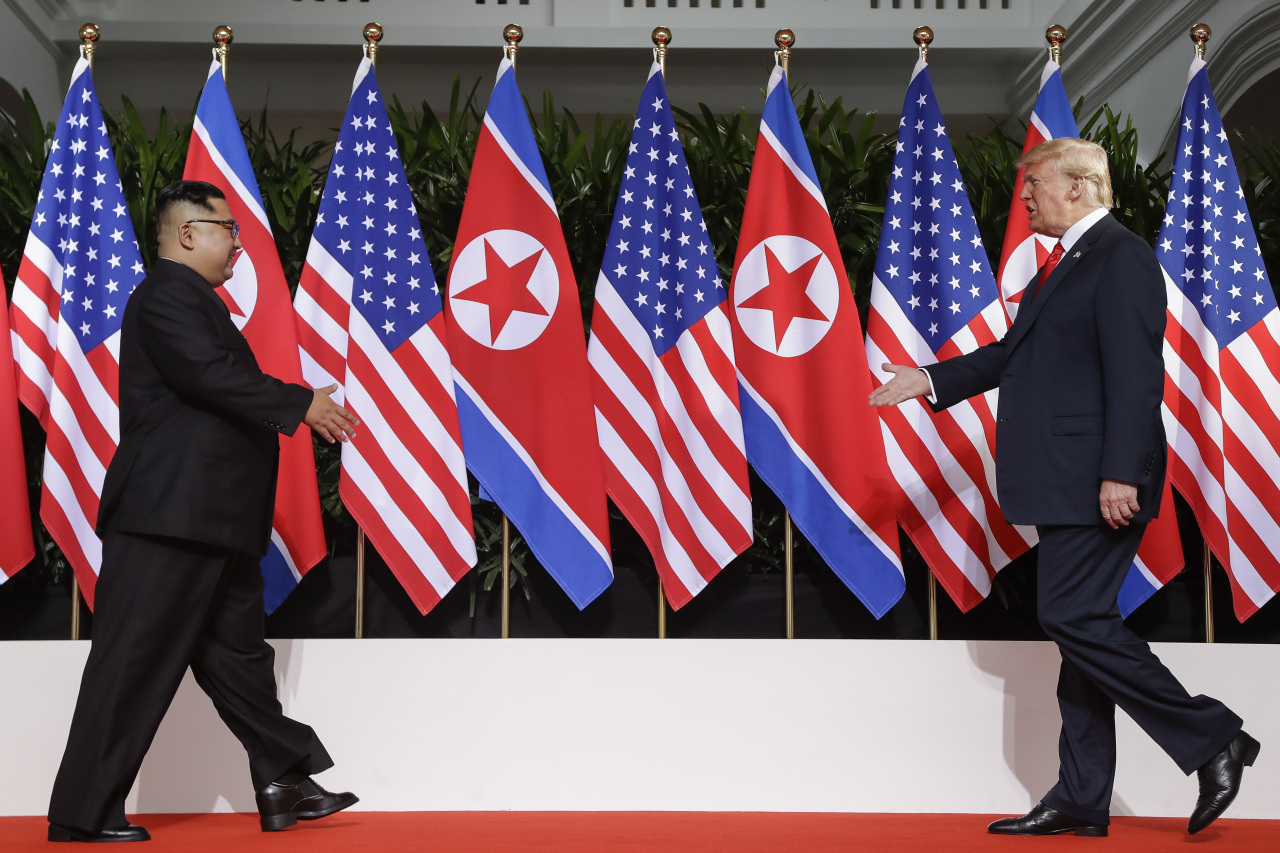 In this June 12, 2018, file photo, US President Donald Trump (right) and North Korea leader Kim Jong Un walk toward each other at the Capella resort on Sentosa Island in Singapore. (AP-Yonhap)