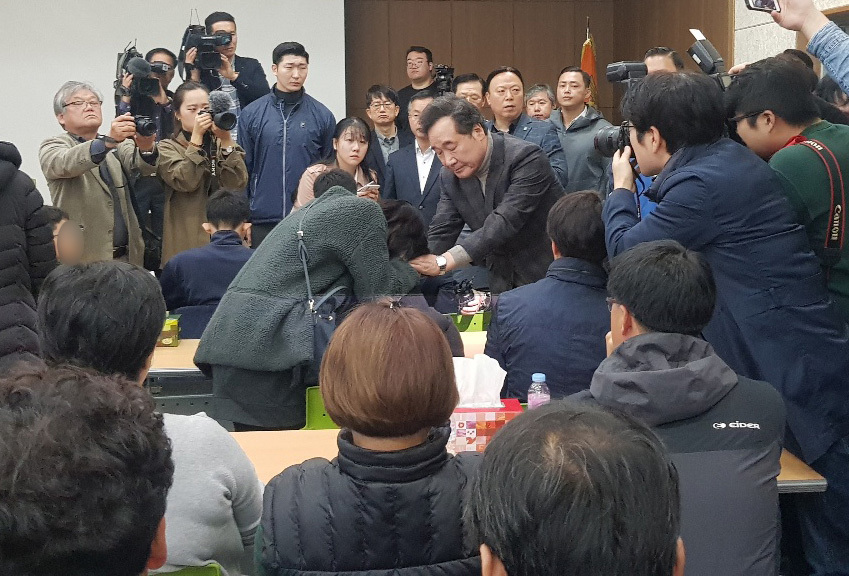 Prime Minister Lee Nak-yon holds hands of a family member of a missing person who was on a rescue helicopter that crashed into the sea off Dokdo last month, during his meeting with other familiy members at a fire station in the southeastern city of Daegu, Saturday. (Yonhap)