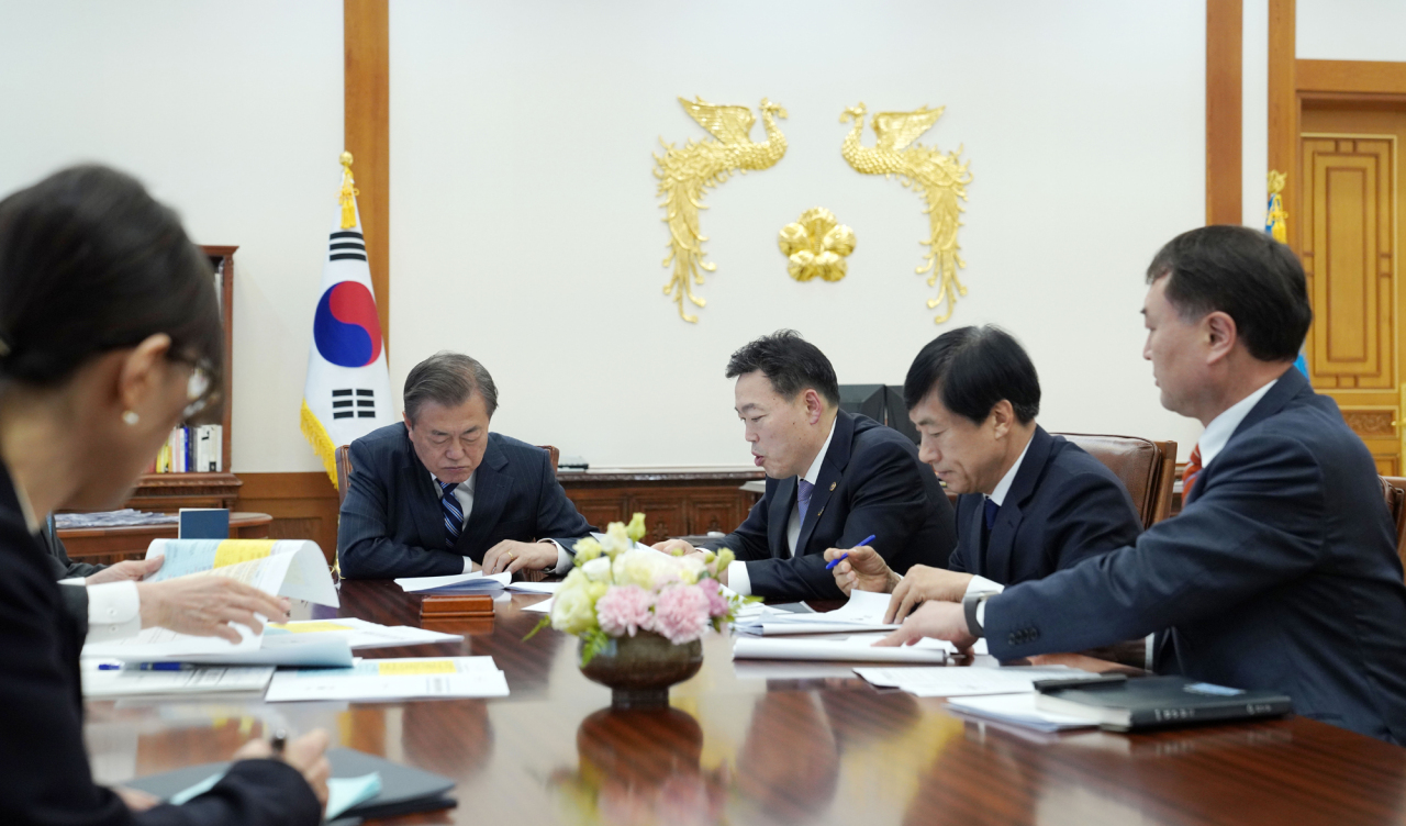 President Moon Jae-in recieves a briefing from Vice Minister of Justice Kim O-su on Friday. Yonhap