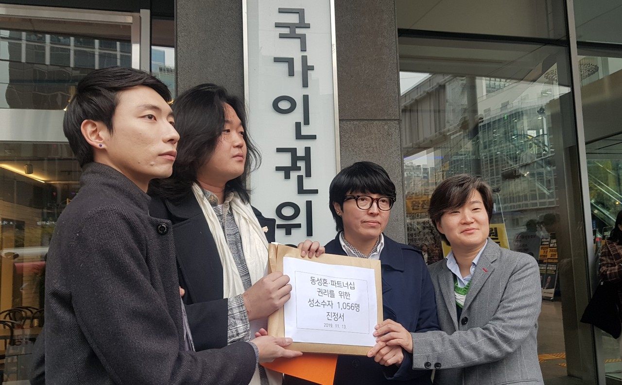From left, Kim Yong-min, Kim`s partner So Sung-uk, Yoon Hwa-young and Yoon`s partner Chang Suh-yeon, hold up the petition document in front of the National Human Rights Commission of Korea building on Wednesday. (Choi Ji-won/ The Korea Herald)