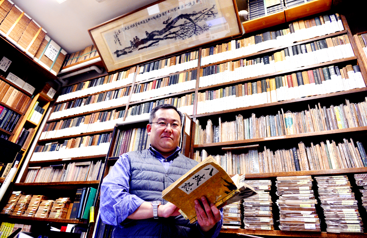 Lee Jong-woon, owner of Tongmunkwan, poses Tuesday in front of the antique books at Tongmunkwan (Park Hyun-koo/The Korea Herald)